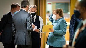 Angela Merkel and her advisors in discussion with French President Emmanuel Macron on the sidelines of a European Council meeting