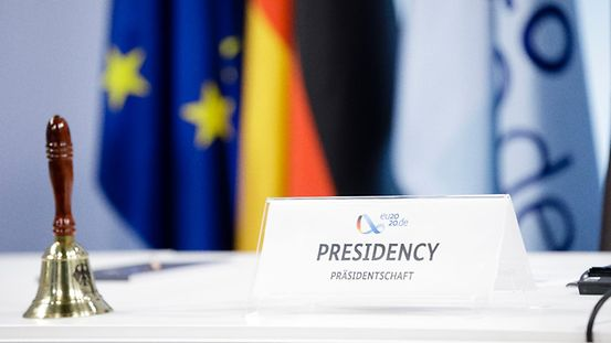 A flag bearing the official logo of Germany's Council Presidency next to those of Germany and the EU