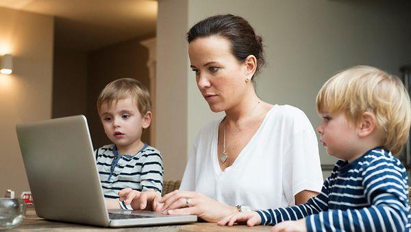 Eine Mutter mit zwei Söhnen arbeitet am Rechner.