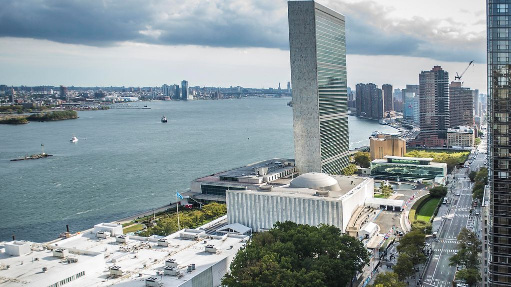 The photo shows the exterior of the United Nations Headquarters.