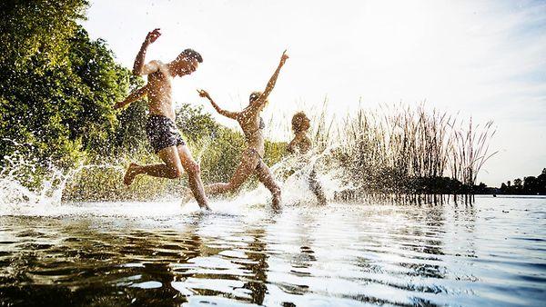 Eine Gruppe von Freunden, die an einem Tag am See zusammen begeistert im Wasser planschen.
