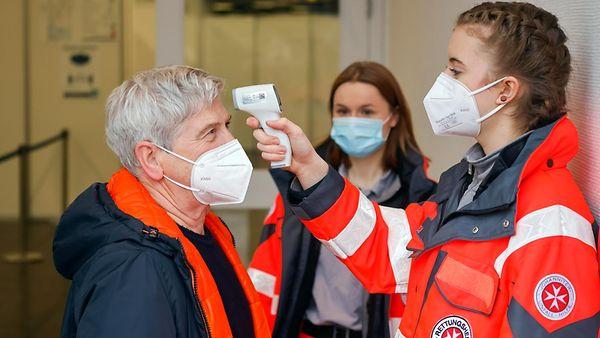Bei einem Testlauf messen Rettungshelferinnen bei einem Impfling die Temperatur.