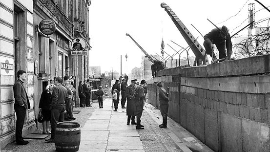 Passers-by on Sebastianstraße (West Berlin side) watch the border soldiers building the wall.