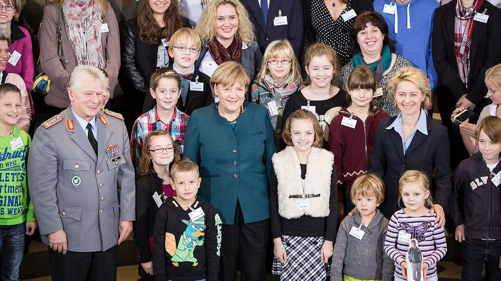 Chancellor Angela Merkel and Ursula von der Leyen, Federal Defence Minister, pose with the families of German soldiers currently serving abroad.