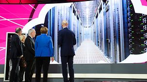 Chancellor Angela Merkel and Swiss President Johann Schneider-Ammann at the Telekom AG stand