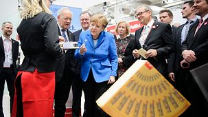 Chancellor Angela Merkel and Swiss President Johann Schneider-Ammann tour the trade fair.