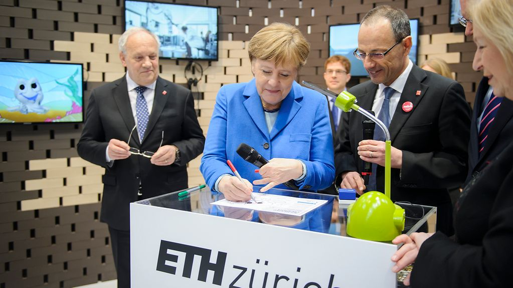 Chancellor Angela Merkel and Swiss President Johann Schneider-Ammann at the ETH Zürich stand during their tour of CeBIT