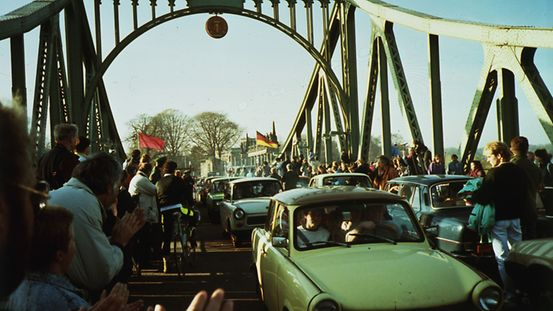 The people of West Berlin welcome visitors from Potsdam on the Glienicke Bridge. An East German Trabant can be seen in the foreground.
