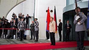 Chancellor Angela Merkel waits in front of the Federal Chancellery.