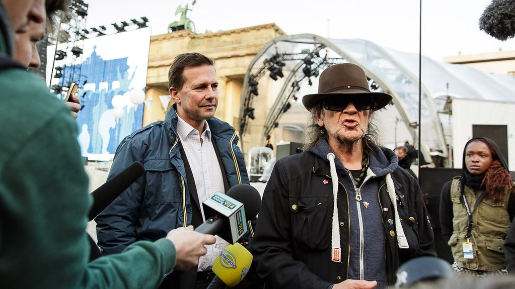 Musician Udo Lindenberg is interviewed as he stands next to government spokesperson Steffen Seibert in frnt of the Brandenburg Gate.