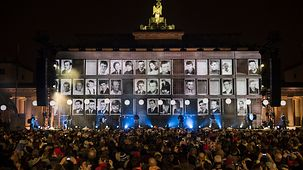 Those who lost their lives at the Berlin Wall are shown on a huge screen.