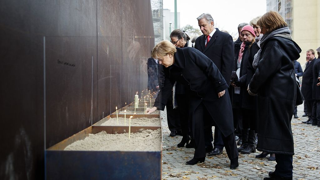 Chancellor Angela Merkel lights a candle at a memorial for victims of Communist violence.