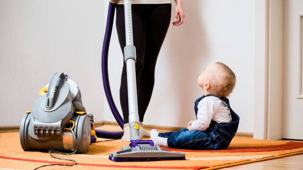 Eine Frau beim Staubsaugen mit Kleinkind.