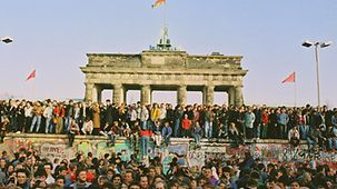People from West and East Berlin stand on and beside the Wall at the Brandenburg Gate.
