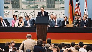 During a speech at the Brandenburg Gate, US President Ronald Reagan declares, 'Mr Gorbachev, open this Gate! Mr Gorbachev, tear down this wall!' (front row from right Eberhard Diepgen, Governing Mayor of Berlin; Chancellor Helmut Kohl;