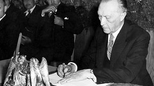 President of the Parliamentary Council, Konrad Adenauer, signs the Basic Law, or constitution, on 23 May 1949 at precisely 17:00 in Bonn.