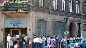 East German citizens queue in front of the Sparkasse in Görlitz to convert their East German marks into D-Marks.