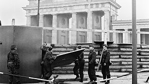 Soldiers of the East German National People's Army build the Berlin Wall, here at the Brandenburg Gate.