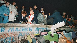 People climb up the West Berlin side of the Wall.