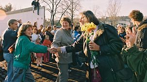 People in West Berlin welcome East Germans with flowers.
