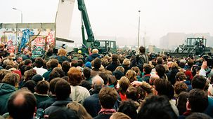 People watch as a crane lifts away a section of the Wall.