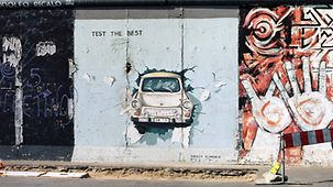 Image of a Trabant breaking through the Wall painted on a Wall section in the East Side Gallery in Berlin