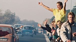 West Germans wave to East German drivers.