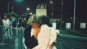 Two women hug at the Invalidenstraße border crossing point.