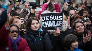 "One demontrator holds high a sign reading ""Je suis Charlie""."