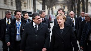 Chancellor Angela Merkel and Federal Economics Affairs Minister Sigmar Gabriel walk side by side.