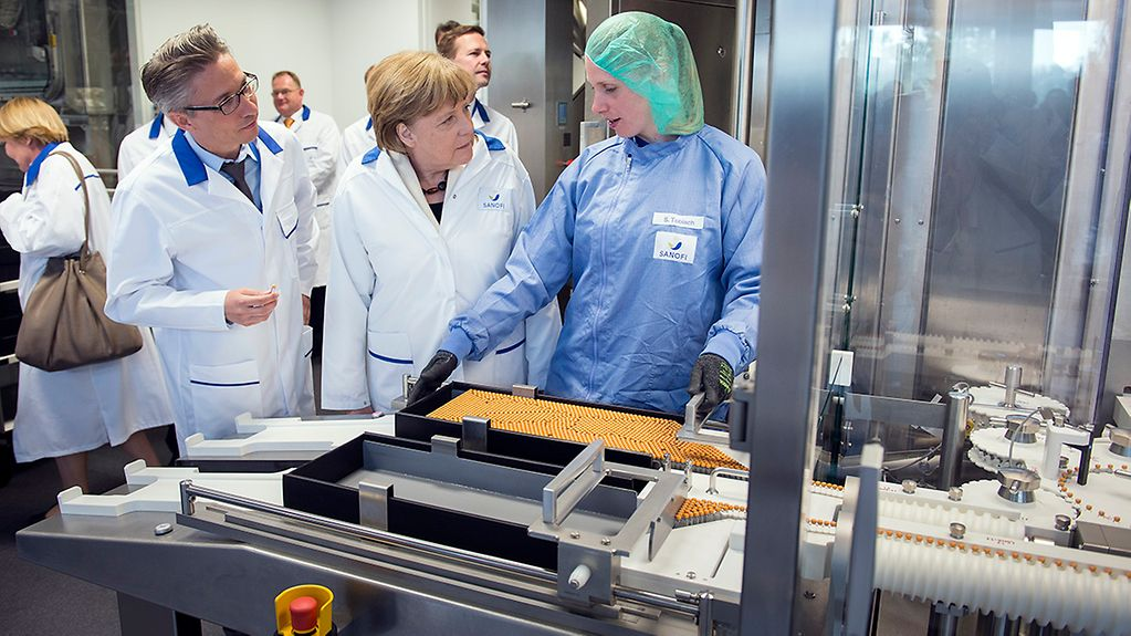 Chancellor Angela Merkel at the cleaning station during her guided tour of the Sanofi plant