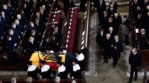 The coffin is carried out of the church.