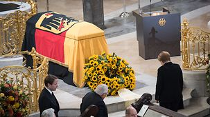 Chancellor Angela Merkel stands, head bowed, in front of Helmut Schmidt's coffin in Hamburg's St. Michael's Church.