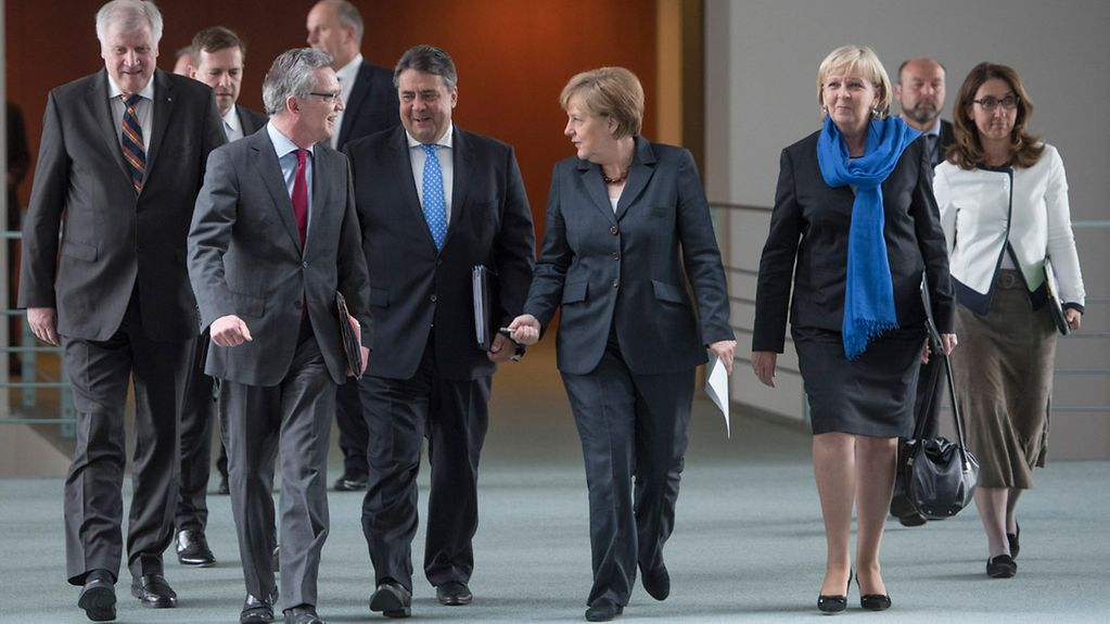 Chancellor Angela Merkel walks to the press conference beside Federal Interior Minister Thomas de Maiziere and Vice-Chancellor Sigmar Gabriel.