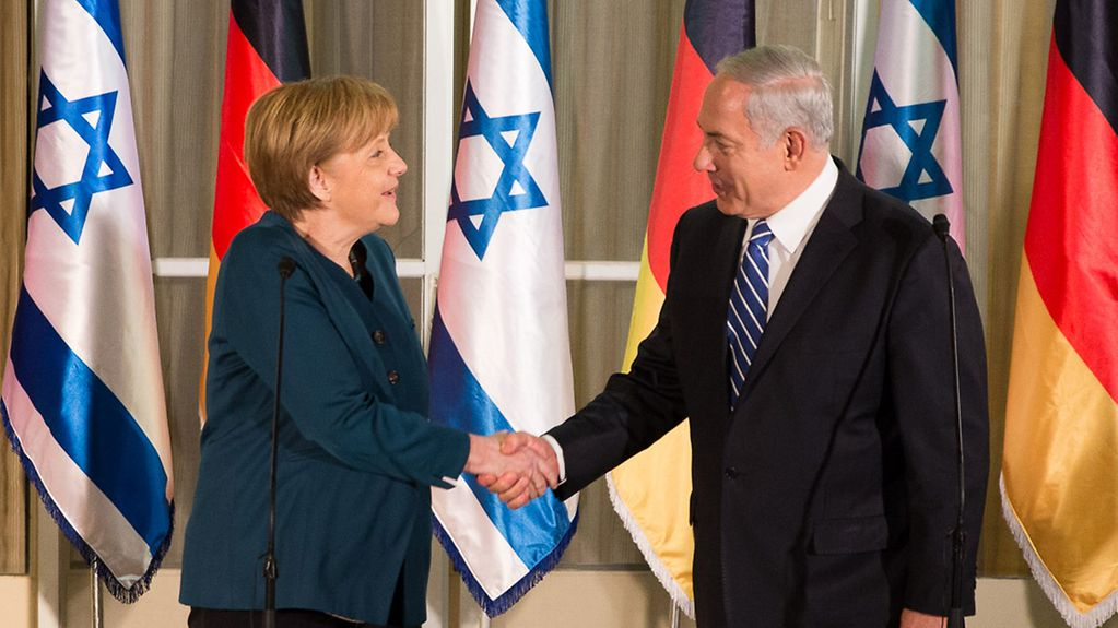 Chancellor Angela Merkel and Prime Minister Benjamin Netanjahu greet one another in front of German and Israeli flags.