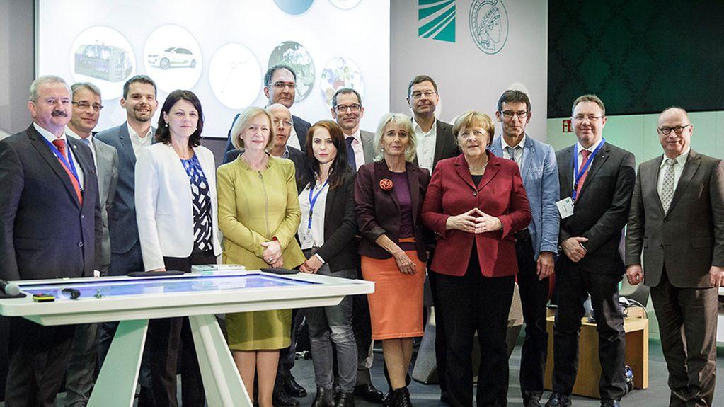 Bundeskanzlerin Angela Merkel (1. Reihe, 6.v.l.), Johanna Wanka, Bundesministerin für Bildung und Forschung (1. Reihe, 3.v.l.), und Rainer Sontowski, Staatssekretär im Bundesministerium für Wirtschaft und Energie (2. Reihe, M.), mit Reimund Neugebauer, …