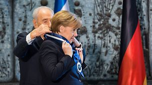 Chancellor Angela Merkel is presented with the Presidential Award of Distinction by Israeli President Shimon Peres.