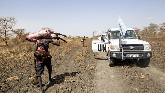 Man from Akobo walks past UN police car with antilope meat near Kuuaibai bridge Photo UNMISS/Martine Perret. 10 April 2013